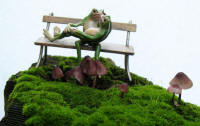 bronze frogs on park bench